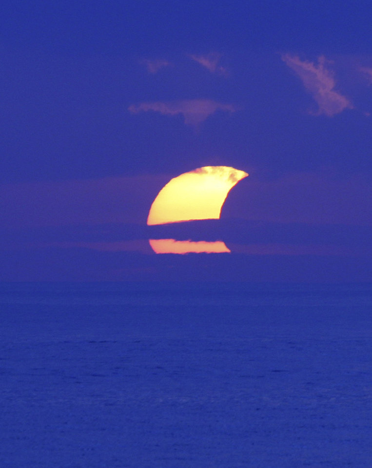 Photo - A partial solar eclipse is seen through cloud at Sanur beach, Bali, Indonesia, Friday, May 10, 2013. (AP Photo/Firdia Lisnawati)