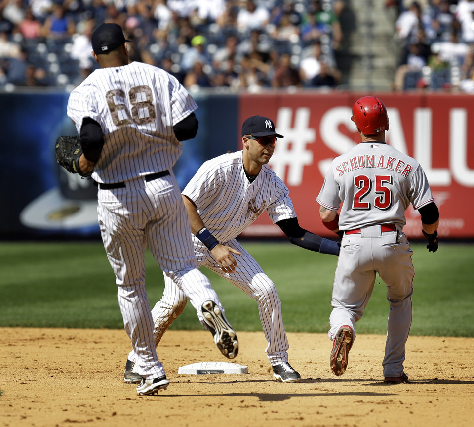 Photo - New York Yankees' Derek Jeter, center, tags out Cincinnati Reds' Skip Schumaker in a run-down during the eighth inning of the game at Yankee Stadium Sunday, July 20, 2014 in New York. (AP Photo/Seth Wenig)
