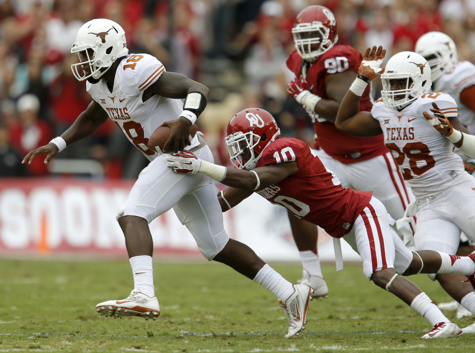 Photo - Texas' Tyrone Swoopes (18) runs past Oklahoma's Quentin Hayes (10) during the Red River Showdown college football game between the University of Oklahoma Sooners (OU) and the University of Texas Longhorns (UT) at the Cotton Bowl in Dallas on Saturday, Oct. 11, 2014. 