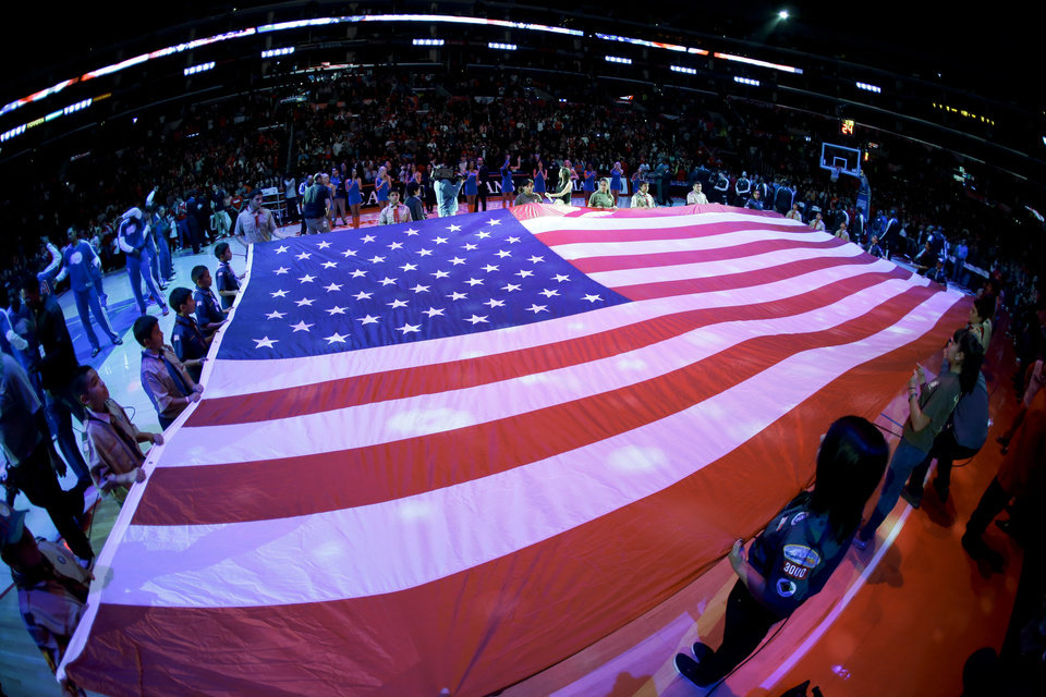 Photo - Local scout troops display a large American flag during the National Anthem before NBA basketball game between the Los Angeles Clippers and the Sacramento Kings in Los Angeles, Friday, Dec. 21, 2012. (AP Photo/Chris Carlson)