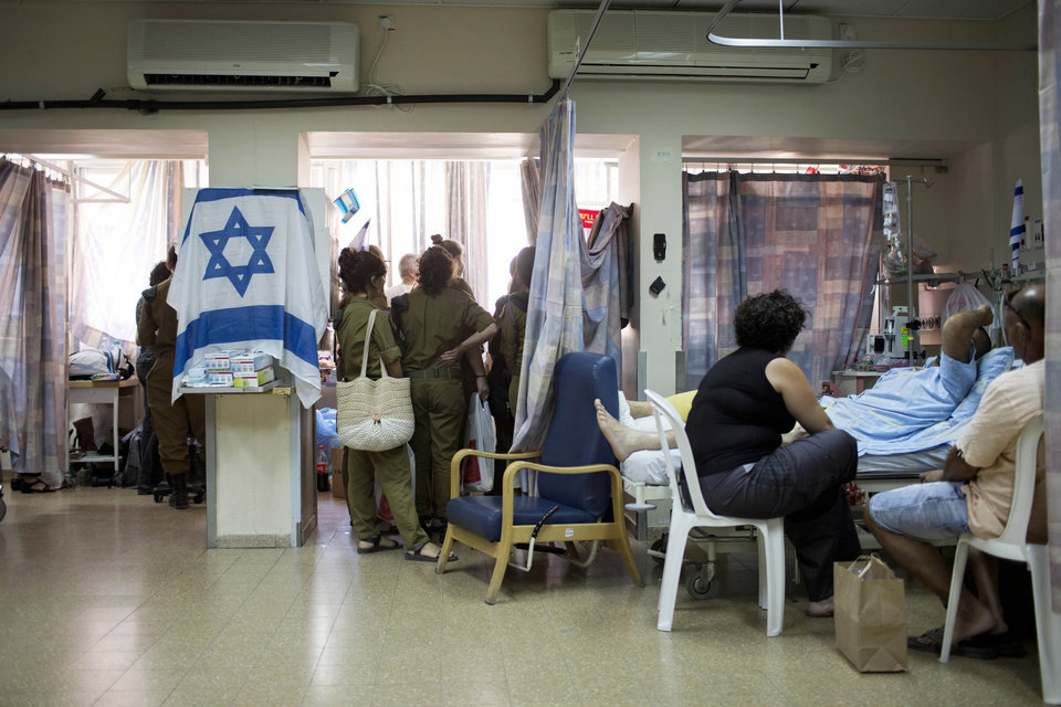 Photo - Israeli soldiers and family members of Israeli soldiers who were wounded during fighting in Gaza, visit them at Soroka hospital In Beer Sheva, southern Israel, Tuesday, July 29, 2014. (AP Photo/Oded Balilty)