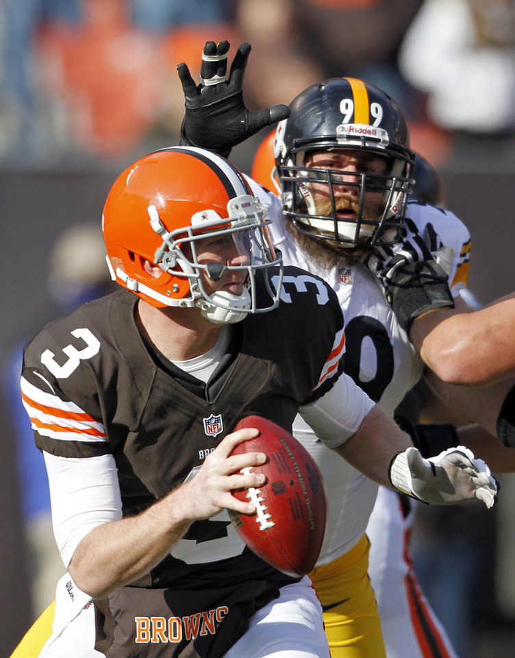 Cleveland Browns quarterback Brandon Weeden (3) is chased by Pittsburgh Steelers defensive end Brett Keisel (99) in the first quarter of an NFL football game Sunday, Nov. 25, 2012, in Cleveland. Weeden was sacked by linebacker James Harrison on the play. (AP Photo/Ron Schwane)