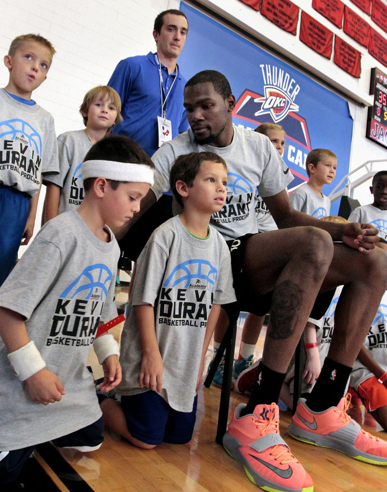 Photo - Kevin Durant pulls Hunter Newman, 6, and jack Barbar, 7, a little closer for a team photograph during Durant's basketball camp on Thursday, Aug. 7, 2014 in Moore, Okla. Photo by Steve Sisney, The Oklahoman