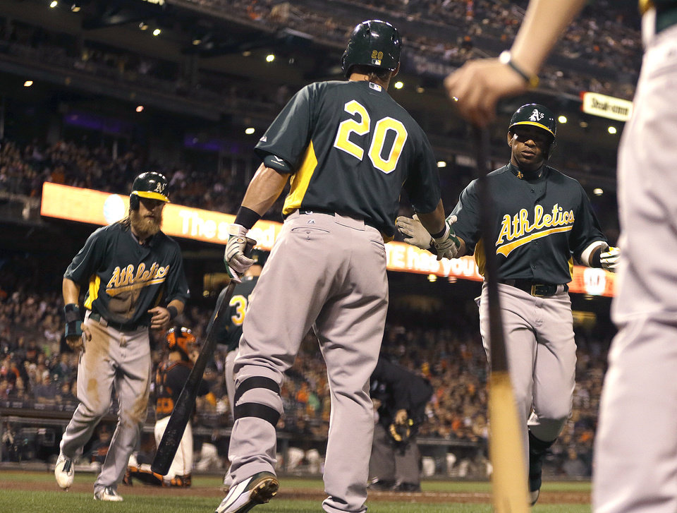 Photo - Oakland Athletics' Yoenis Cespedes, right, is congratulated by Josh Donaldson (20) after Cespedes hit a two-run home run off San Francisco Giants' Tim Lincecum in the fourth inning of an exhibition spring training baseball game, Thursday, March 28, 2013, in San Francisco. (AP Photo/Ben Margot)