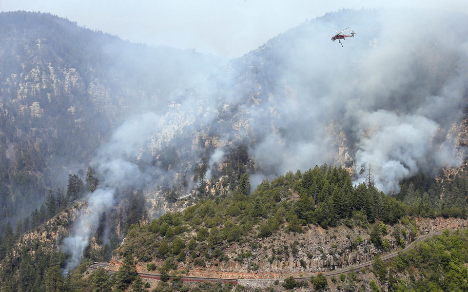 Photo - A Heavy Type-1 Skycrane Helictoper flies over the Slide Fire, above the route 89 A, before dumping a 2,000 gallon load of water as it burns up Oak Creek Canyon on Friday, May 23, 2014, near Flagstaff, Ariz.  The fire has burned approximately 7,500 acres and is five percent contained. (AP Photo/Ross D. Franklin)