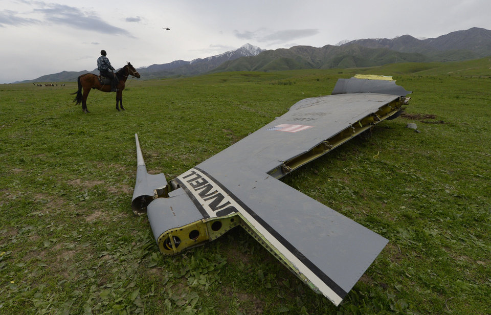 Photo - A U.S. Air Force KC-135 tanker aircraft wreckage is strewn across a field near the village of Chaldovar, about 100 miles (160 kms) west of the Kyrgyz capital Bishkek, Friday May 3, 2013. The emergencies ministry in Kyrgyzstan says a US military plane has crashed in the country. Kyrgyzstan hosts a US base that is used for troops transiting into and out of Afghanistan and for C-135 tanker planes that refuel warplanes in flight. (AP Photo/Vladimir Voronin)