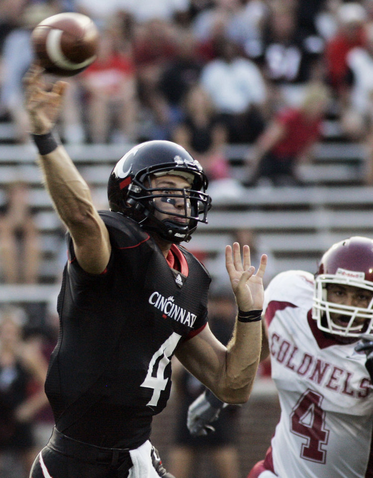 Photo - University of Cincinnati quarterback Dustin Grutza, left, passes against Eastern Kentucky defender Chris Coy during the first half of a college football game, Thursday, Aug. 28, 2008, in Cincinnati. (AP Photo/Al Behrman) ORG XMIT: OHAB101