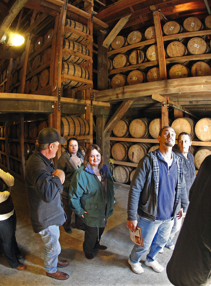 Photo - FILE -- This Nov. 27, 2009 file photo shows visitors viewing barrels of aging whiskey while on a tour of the Jack Daniel's distillery in Lynchburg, Tenn. The 70-mile trip from Nashville to Lynchburg offers a free tour of the oldest registered American distillery. (AP Photo/Mark Humphrey, File)