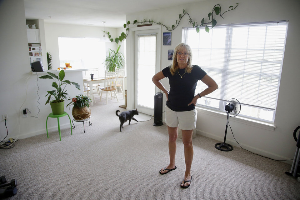 Photo - Julie Pemberton stands in the living room of her apartment as her cat Pewter walks through, Thursday, June 26, 2014, in Weymouth, Mass. Pemberton works more than 40 hours a week during the academic year. That gave her access to health care on the job until her employer changed the rules ahead of new coverage requirements under President Barack Obama's health care law. The workers, their union, and even some college administrators, say the government appears to have unwittingly created a loophole that's hurting employees the law was intended to help.  (AP Photo Stephan Savoia)