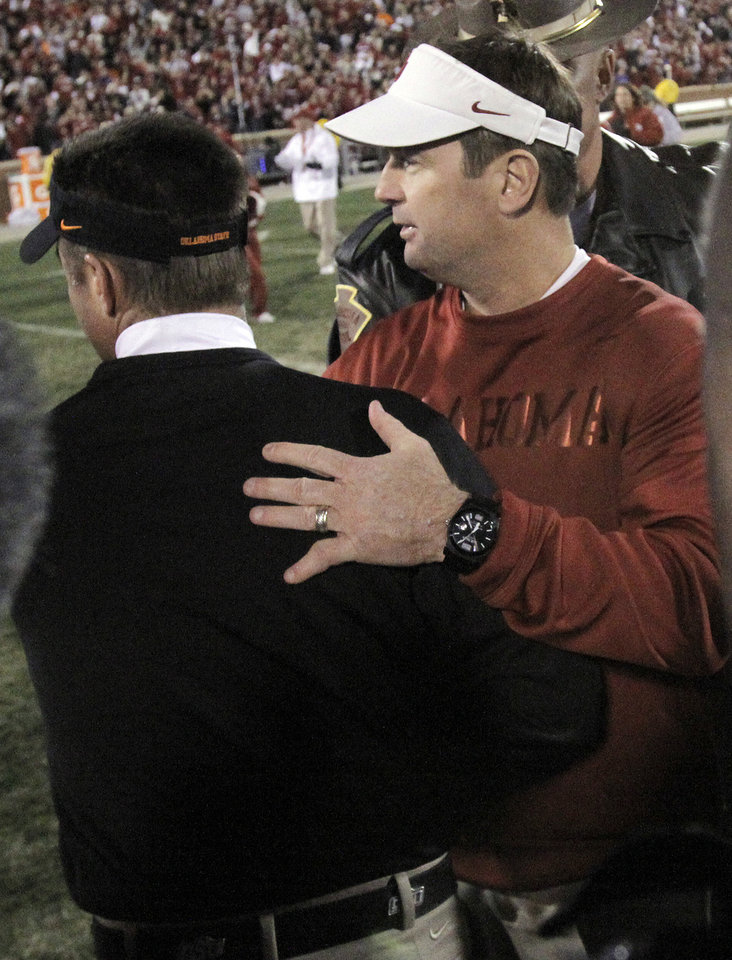 Photo - Oklahoma head coach Bob Stoops greets Oklahoma State coach Mike Gundy following the Bedlam college football game between the University of Oklahoma Sooners (OU) and the Oklahoma State University Cowboys (OSU) at Gaylord Family-Oklahoma Memorial Stadium in Norman, Okla., Saturday, Nov. 24, 2012. OU won 51-48 in overtime. Photo by Sarah Phipps, The Oklahoman