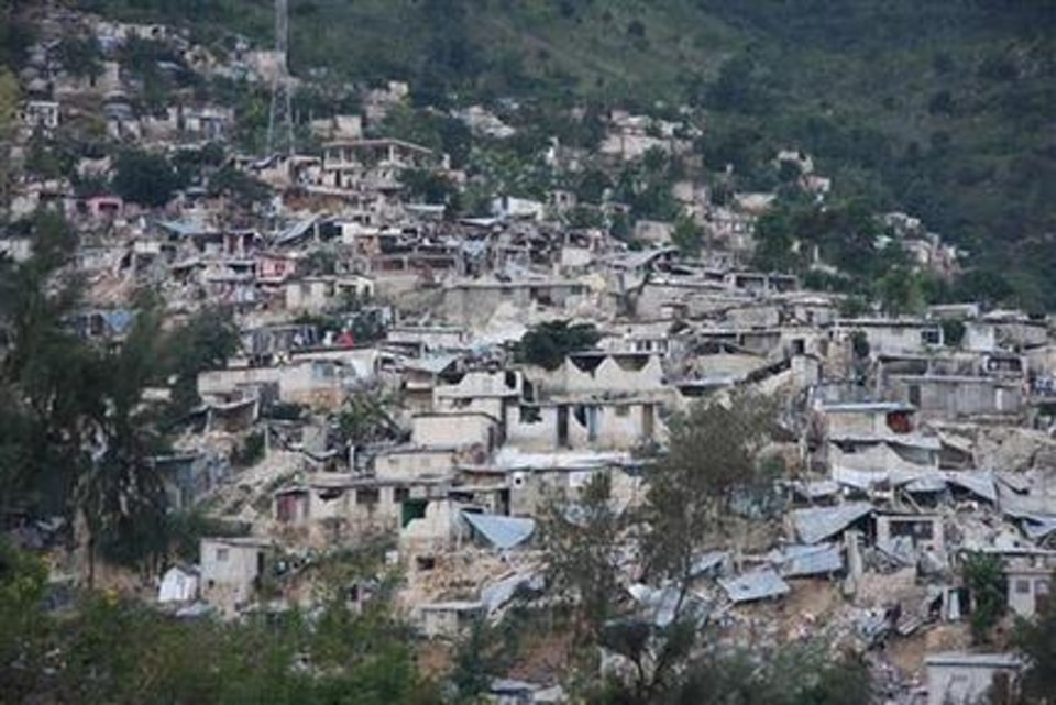 Photo - n this image made available by the American Red Cross in London, Wednesday Jan. 13, 2010 shows earthquake  damage to a shanty town on the outskirts of Port au Prince, following a major earthquake in Haiti, Tuesday Jan. 12, 2010. Haitians piled bodies along the devastated streets of their capital Wednesday after the strongest earthquake to hit the poor Caribbean nation in more than 200 years crushed thousands of structures, from schools and shacks to the National Palace and the U.N. peacekeeping headquarters. Untold numbers were still trapped.(AP Photo/American Red Cross, Matt Marek)    EDITORIAL USE ONLY