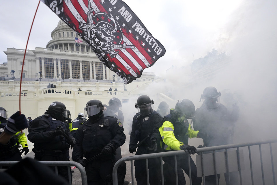 Photo - Police hold off Trump supporters who tried to break through a police barrier, Wednesday, Jan. 6, 2021, at the Capitol in Washington. As Congress prepares to affirm President-elect Joe Biden's victory, thousands of people have gathered to show their support for President Donald Trump and his claims of election fraud. (AP Photo/Julio Cortez)