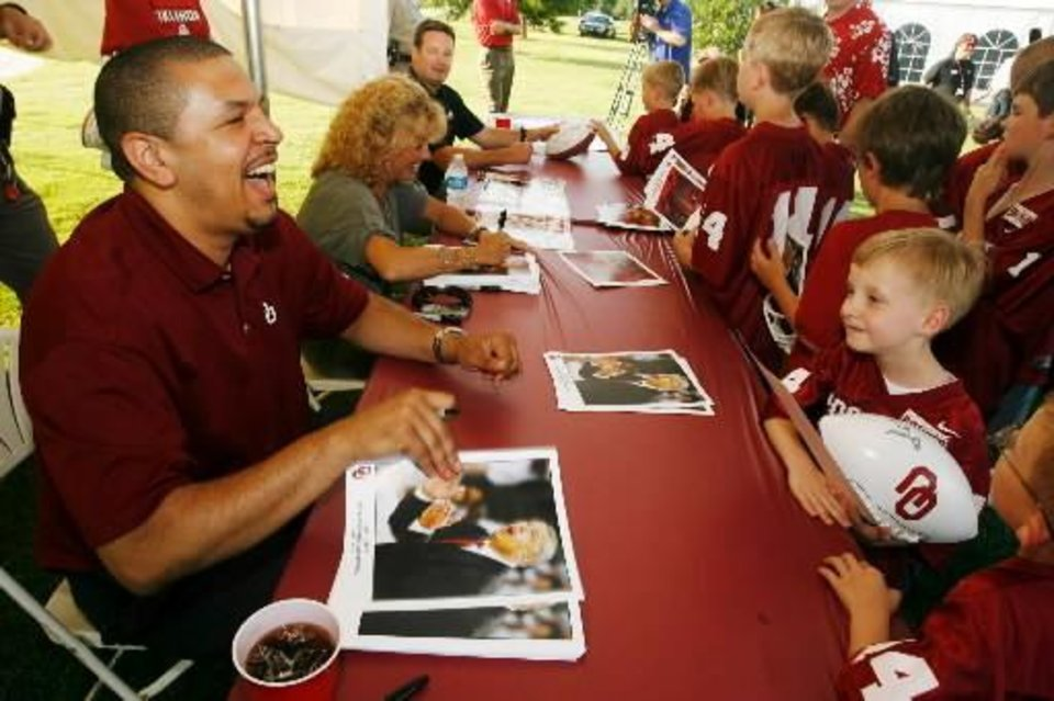 Photo - OU: University of Oklahoma men's college basketball coach Jeff Capel, left, jokes with fans, including Ford Luessenhop, 7, from Tulsa, in Tulsa, Okla., on Tuesday, May 25, 2010 during a Sooner Caravan visit to Tulsa. (AP Photo/Tulsa World, James Gibbard) ORG XMIT: OKTUL102
