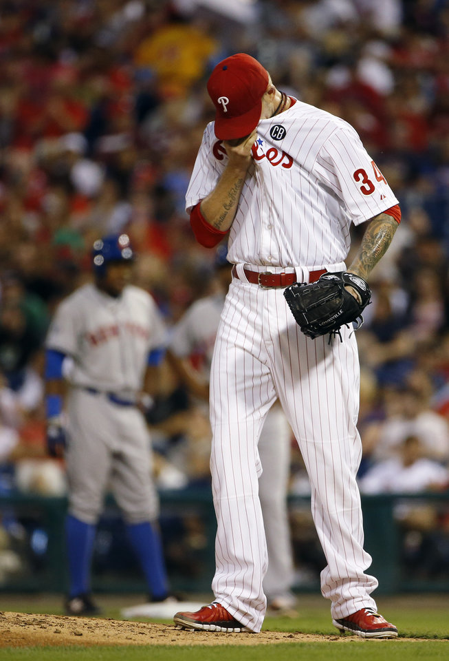 Photo - Philadelphia Phillies' A.J. Burnett, right, wipes his face after giving up an RBI-single to New York Mets' Curtis Granderson during the fourth inning of a baseball game, Friday, Aug. 8, 2014, in Philadelphia. (AP Photo/Matt Slocum)