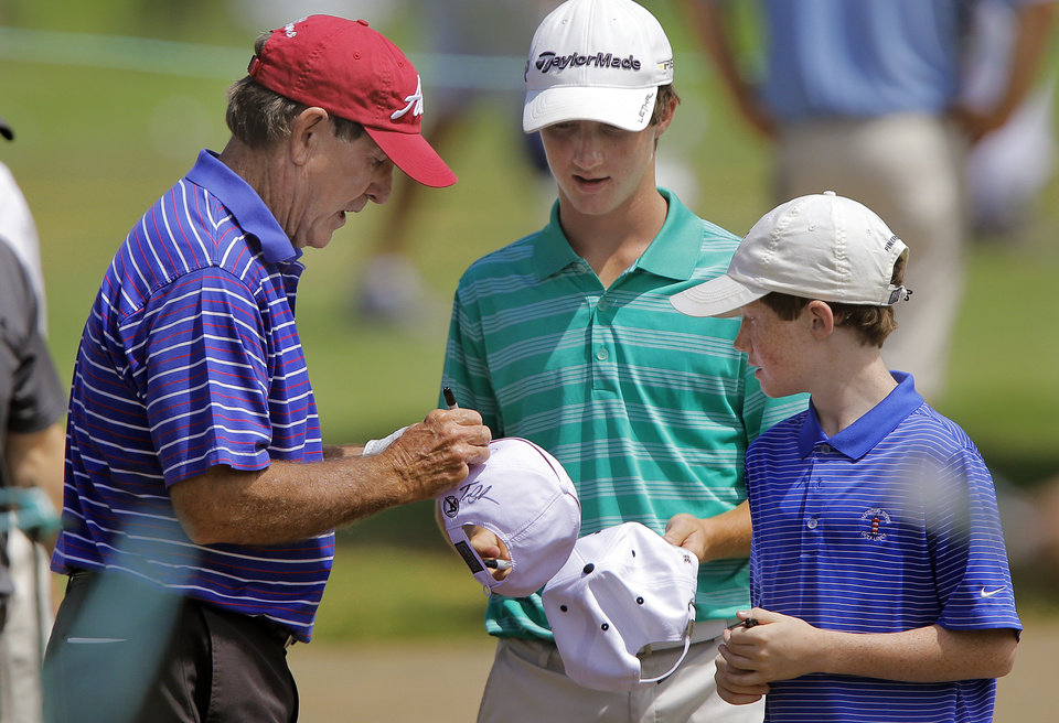 Photo - Gil Morgan signs an autograph for brothers Nick and Jake O'Donnell, from left, during practice rounds for the U.S. Senior Open golf tournament at Oak Tree National in Edmond, Okla. on Wednesday, July 9, 2014. Photo by Chris Landsberger, The Oklahoman