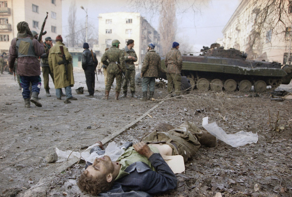 EDS NOTE: GRAPHIC CONTENT - FILE -A Russian soldier lies dead as Chechen fighters gather next to a tank outside the presidential palace in central Grozny, in this Jan. 3, 1994 file photo as Russian troops and Chechen fighters battled for control of the breakaway capital. Two suspects in the Boston Marathon bombing have been identified to The Associated Press as coming from a Russian region near Chechnya In the past, insurgents from Chechnya and neighboring restive provinces in the Caucasus have been involved in terror attacks in Moscow and other places in Russia. (AP Photo/David Brauchli, File)