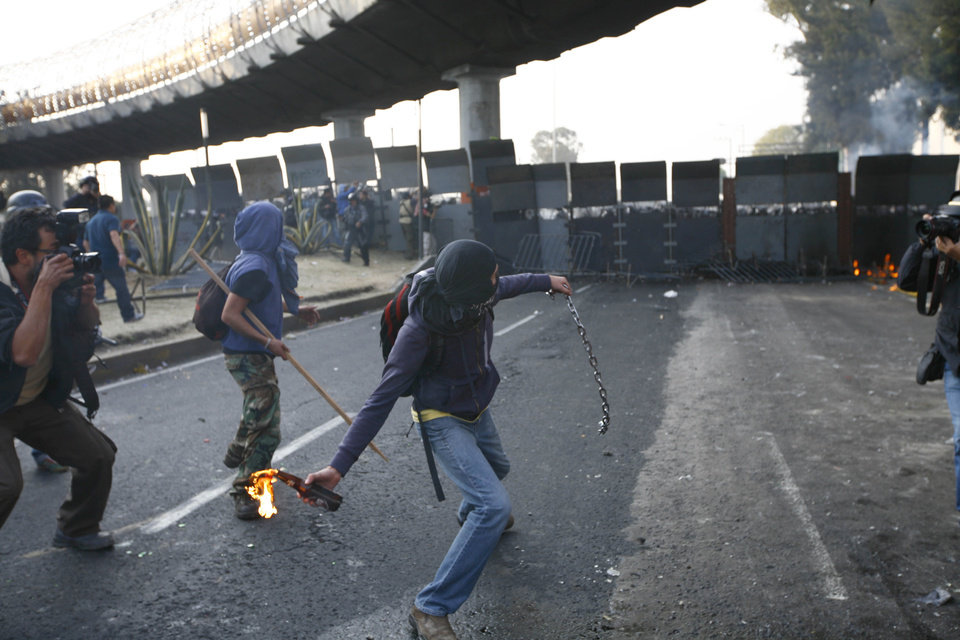 CORRECTS DAY OF THE WEEK TO SATURDAY .- A protestor throws a fire bottle over steel security barriers around the National Congress, where the swearing in of new Mexican President Enrique Pena Nieto will take place in Mexico City, Saturday Dec. 1, 2012.  Pena Nieto took power at midnight in a symbolic ceremony and will formally take the oath of office Saturday morning after campaigning as the face of a new PRI _ a party that claims to be repentant and reconstructed after voted out of the presidency in 2000.(AP Photo / Marco Ugarte)