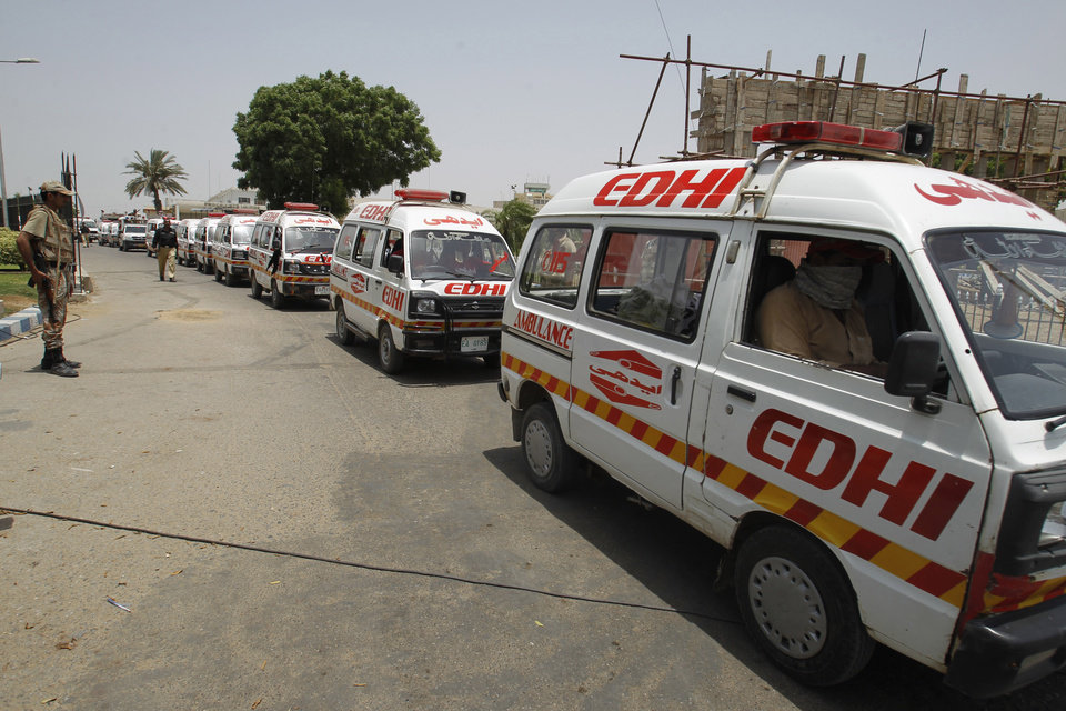 Photo - Ambulances carry bodies of attackers to hospital from the Jinnah International Airport in Karachi, Pakistan, Monday, June 9, 2014. The Pakistani Taliban on Monday claimed responsibility for a brazen five-hour assault on the country's busiest airport that saw gunmen disguised as police guards storm the international terminal in Karachi, set off explosions and killing over a dozen of people. (AP Photo/Fareed Khan)