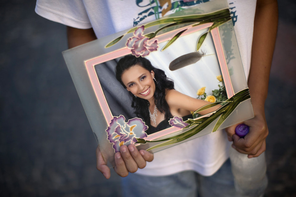 A youth holds a photograph of his sister Pamella Lopes, who died in a nightclub fire, in a public square near the club in Santa Maria, Brazil, Monday, Jan. 28, 2013. A fast-moving fire roared through the crowded, windowless Kiss nightclub in this southern Brazilian city early Sunday, killing more than 230 people. Many of the victims were under 20 years old, including some minors. (AP Photo/Felipe Dana) ORG XMIT: XFD117