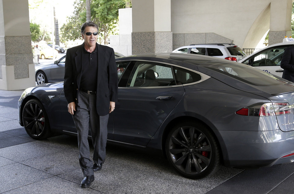 Photo - File - In this June 10, 2014 file photo, Texas Gov. Rick Perry walks over to talk to reporters after driving up in a Tesla Motors Type S electric car in Sacramento, Calif. Texas and California are two of five states where Tesla Motors is considering building a $5 billion factory to make batteries for a new model of electric car. (AP Photo/Rich Pedroncelli, File)