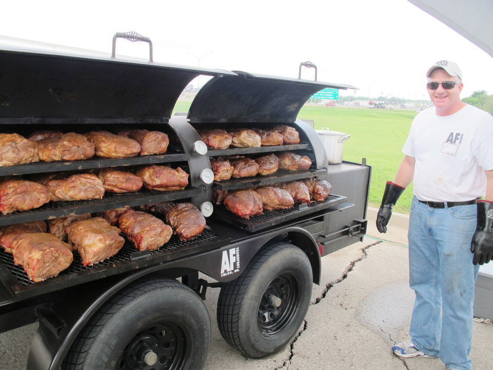 Photo - Paul Peterson, of Tulsa, came in last week to prepare pork loins in his industrial mobile smoker out of gratitude for Mother Nature. Photo by Dave Cathey, The Oklahoman