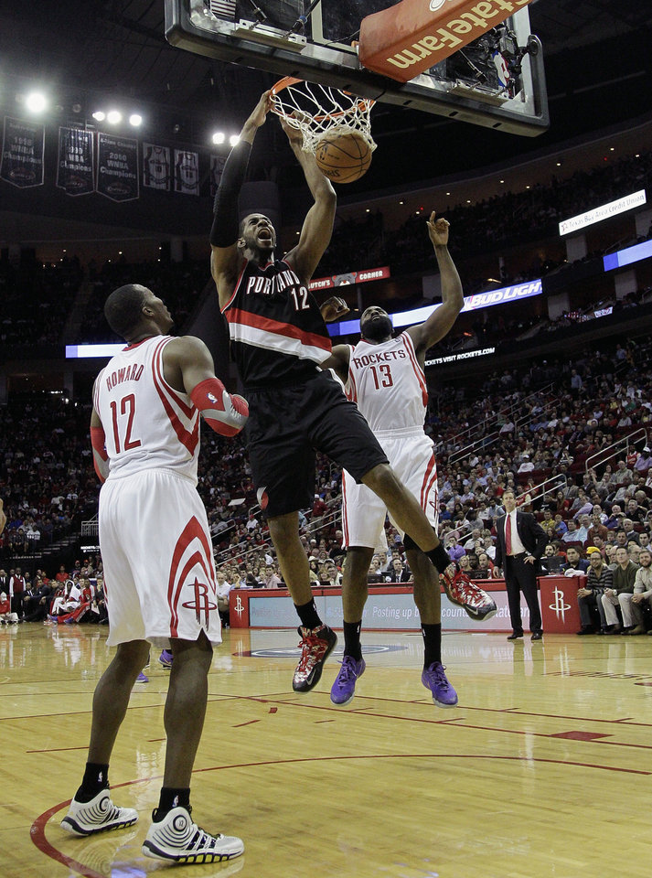 Photo - Portland Trail Blazers forward LaMarcus Aldridge (12) dunks between Houston Rocket's Dwight Howard (12) and James Harden (13) during the first half of an NBA basketball game, Monday, Jan. 20, 2014, in Houston. (AP Photo/Bob Levey)