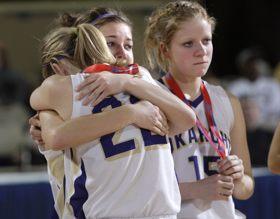 Photo - Okarche's Rae Grellner hugs Kanadey Greller (22) as Madi Grellner stands next to them following their loss to Frontier in the championship game of the girls Class A state basketball tournament at the State Fair Arena in Oklahoma City,  Saturday, March 3, 2012. Photo by Sarah Phipps, The Oklahoman