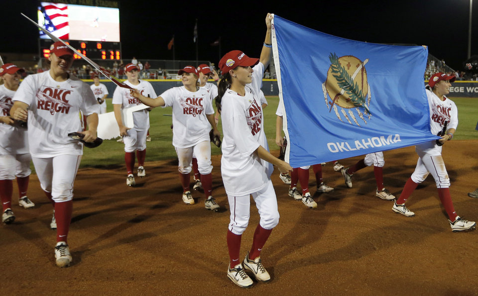 The Sooner's carry an Oklahoma flag following their win in  Women's College World Series softball game between Oklahoma and Tennessee at ASA Hall of Fame Stadium in Oklahoma City,Tuesday, June, 4, 2013. Photo by Sarah Phipps, The Oklahoman