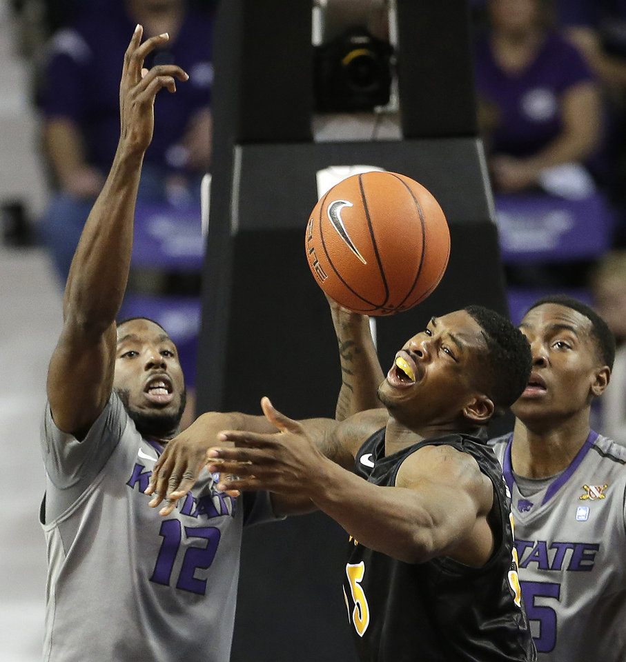 Photo - Kansas State's Omari Lawrence (12) knocks the ball away from Long Beach State's Dan Jennings, center, during the first half of an NCAA college basketball game Sunday, Nov. 17, 2013, in Manhattan, Kan. (AP Photo/Charlie Riedel)