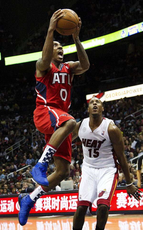 Atlanta Hawks point guard Jeff Teague (0) drives to the basket as Miami Heat point guard Mario Chalmers (15) watches in the first half of an NBA basketball game in Atlanta, Friday, Nov. 9, 2012. (AP Photo/John Bazemore)