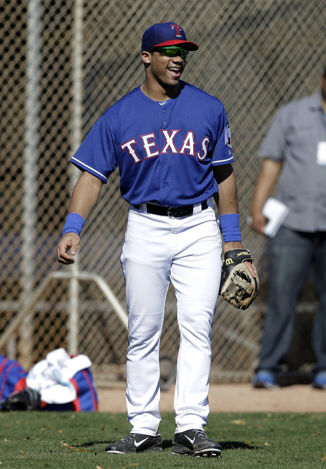Photo - Seattle Seahawks quarterback Russell Wilson stands on the practice field as he works out with the Texas Rangers during spring training baseball practice, Monday, March 3, 2014, in Surprise, Ariz. (AP Photo/Tony Gutierrez)