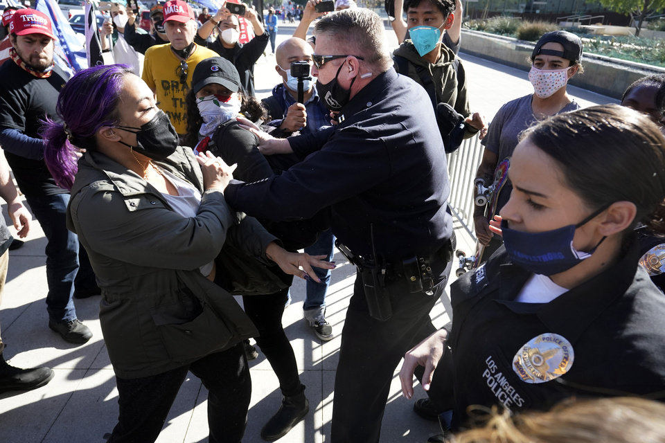 Photo - Police shove two counter demonstrators during a pro-Trump rally outside of police headquarters Wednesday, Jan. 6, 2021, in Los Angeles. Demonstrators, supporting President Donald Trump, are gathering in various parts of Southern California as Congress debates to affirm President-elect Joe Biden's electoral victory. (AP Photo/Marcio Jose Sanchez)