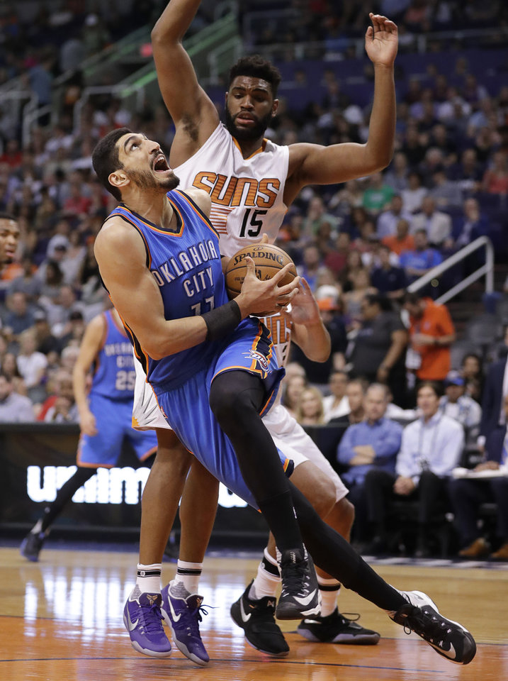 Photo - Oklahoma City Thunder center Enes Kanter falls as Phoenix Suns forward Alan Williams (15) defends during the first half of an NBA basketball game, Friday, April 7, 2017, in Phoenix. (AP Photo/Matt York)