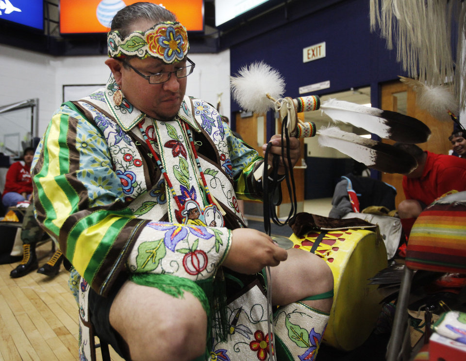 Photo -  Matt Littlecreek, of Oklahoma City, pieces together his headdress before a dance at the University of Central Oklahoma's annual Spring Powwow. PHOTO BY K.T. KING, THE OKLAHOMAN   KT King -