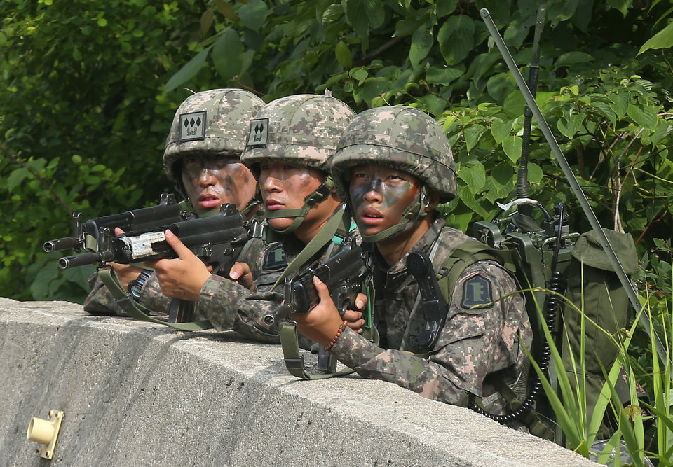 Photo - South Korean army soldiers aim their machine guns during an arrest operation in Goseong, South Korea, Monday, June 23, 2014. The parents of a runaway South Korean soldier suspected of killing five comrades at an outpost near the tense border with North Korea pleaded with him to surrender Monday as the military were besieging him and trying to capture him alive, officials said. (AP Photo/Yonhap, Hwang Kwang-mo)  KOREA OUT