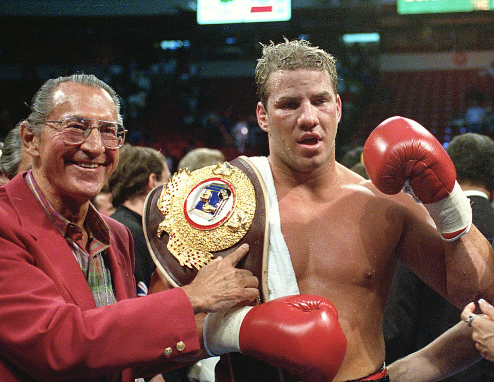 """Photo - FILE - In this June 7, 1993 file photo, newly crowned WBO heavyweight champion Tommy Morrison receives his championship belt after defeating George Foreman in Las Vegas, Nev. Morrison, a former heavyweight champion who gained fame for his role in the movie """"Rocky V,"""" has died. He was 44. Morrison's former manager, Tony Holden says his longtime friend died Sunday night, Sept. 1, 2013, at a Nebraska hospital.  (AP Photo/Nick Ut, File)"""