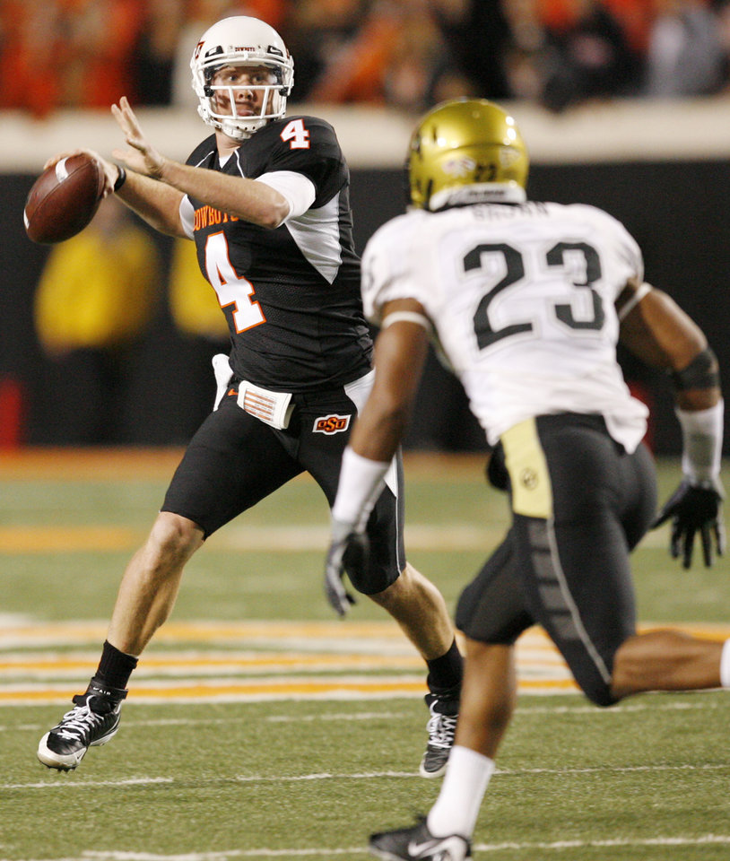 Photo - OSU's Brandon Weeden (4) throws a touchdown pass in the fourth quarter as Jalil Brown (23) of Colorado defends during the college football game between Oklahoma State University (OSU) and the University of Colorado (CU) at Boone Pickens Stadium in Stillwater, Okla., Thursday, Nov. 19, 2009. OSU won, 31-28. Photo by Nate Billings, The Oklahoman