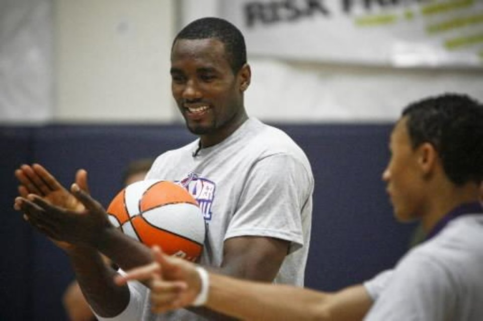 Photo - Serge Ibaka laughs during a drill at the Thunder Youth Basketball Camp at the Santa Fe Family Life Center on Tuesday, June 14, 2011. Photo by Zach Gray