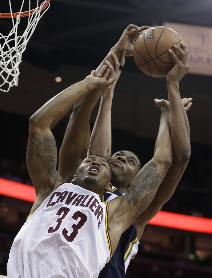 Cleveland Cavaliers' Alonzo Gee, front, and Utah Jazz's Derrick Favors go up for a rebound during the second quarter of an NBA basketball game Wednesday, March 6, 2013, in Cleveland. (AP Photo/Tony Dejak)