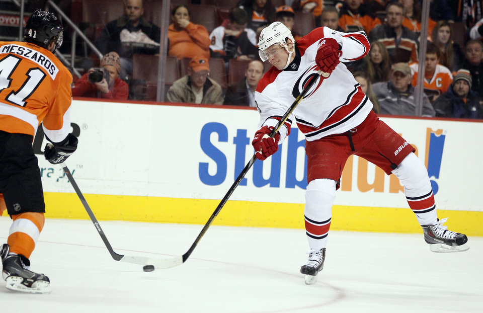 Photo - Carolina Hurricanes' Alexander Semin, right, launches a wrist shot past Philadelphia Flyers' Andrej Meszaros that went in for a goal during the first period of an NHL hockey game, Wednesday, Jan. 22, 2014, in Philadelphia.  (AP Photo/Tom Mihalek)