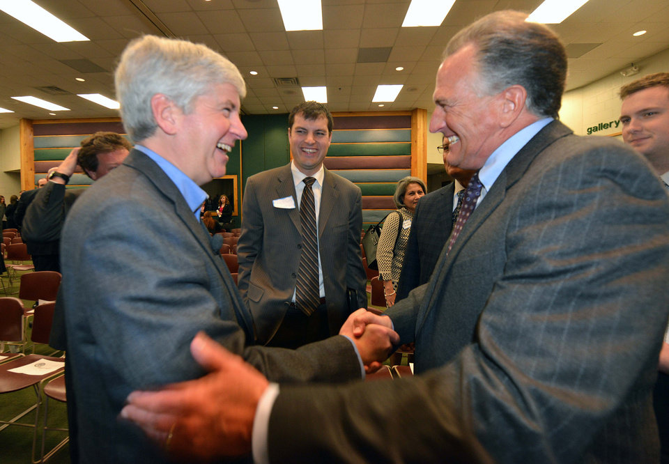 John Russell of Consumers Energy, right, greets Governor Rick Snyder after he presented his views on Michigan's future energy plans and how they merge with environmental and resource management issues at MSU's WK Kellogg Biological Station, Wednesday, Nov. 28, 2012 near Hickory Corners, Mich. (AP Photo/Detroit News, Dale G. Young) DETROIT FREE PRESS OUT; HUFFINGTON POST OUT