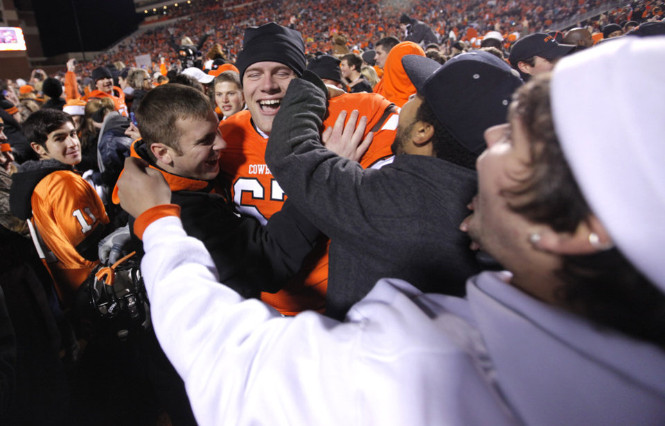 Photo - Oklahoma State's Caleb Thyer (67) celebrates with fans after the 44-10 win over Oklahoma during the Bedlam college football game between the Oklahoma State University Cowboys (OSU) and the University of Oklahoma Sooners (OU) at Boone Pickens Stadium in Stillwater, Okla., Saturday, Dec. 3, 2011. Photo by Chris Landsberger, The Oklahoman