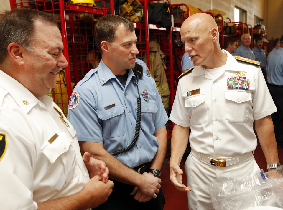 Photo - Rear Adm. Sean A. Pybus, commander, Naval Special Warfare Command, talks with Deputy Chief Jim Bailey, left, and Driver Jason Smith as he meets Norman Fire Department officers and firefighters on Thursday, Sept. 13, 2012 in Norman, Okla.  Photo by Steve Sisney, The Oklahoman