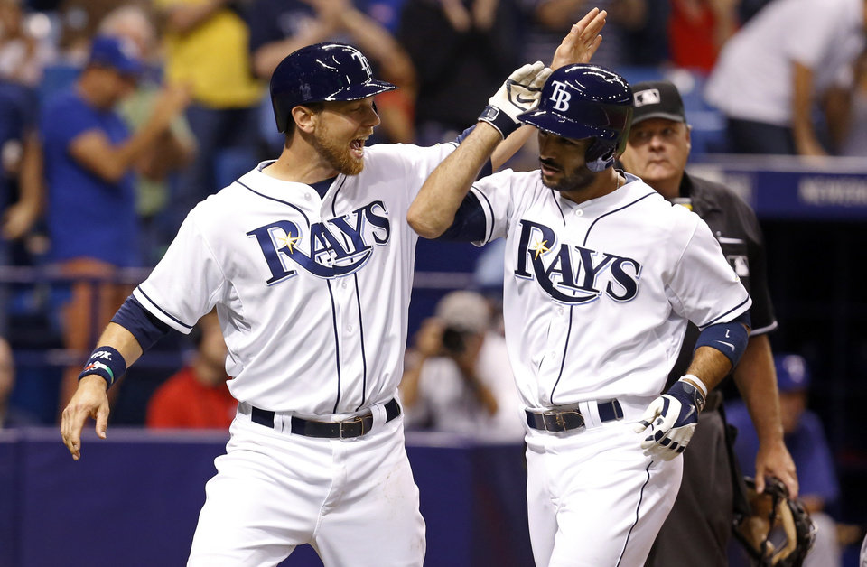 Photo - Tampa Bay Rays' Sean Rodriguez, right, is congratulated on his three-run home run against the Texas Rangers by teammate Ben Zobrist during the third inning of a baseball game Friday, April 4, 2014, in St. Petersburg, Fla. (AP Photo/Mike Carlson)