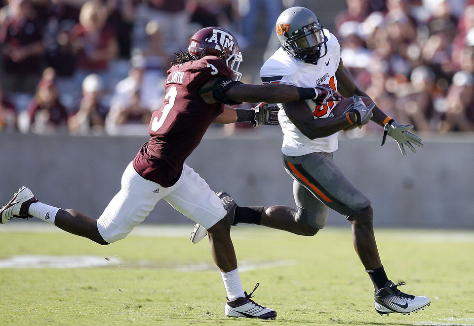Oklahoma State 's Justin Blackmon tries to get by Texas A&M 's Lionel Smith in the second half of the Cowboys' 30-29 win on Saturday in College Station, Texas. Photo by Sarah Phipps, The Oklahoman