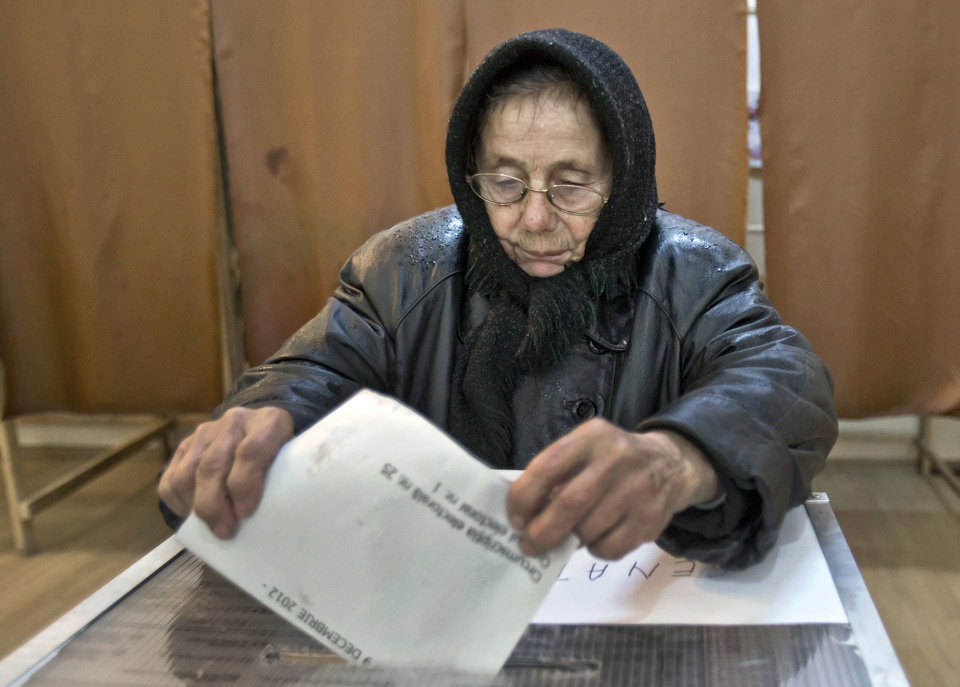 An elderly woman casts a ballot in Sintesti, Romania, Sunday, Dec. 9, 2012. Millions of Romanians braved rain and snow Sunday as they went to the polls for a parliamentary election that center-left government is expected to win a, but the result could lead to more of the political instability that has plagued the impoverished Balkan nation this year. (AP Photo/Vadim Ghirda)