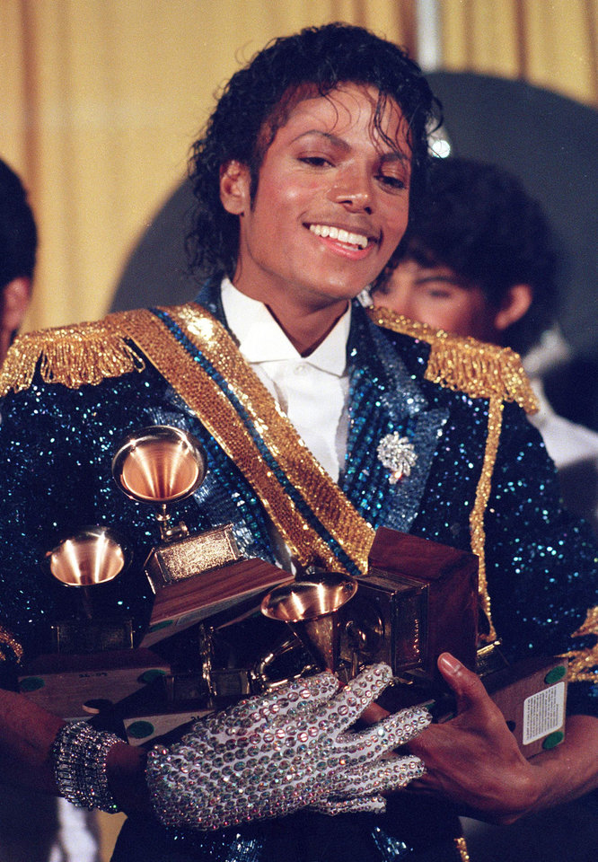 Photo - FILE - In this Feb. 28, 1984 file photo, Michael Jackson is seen backstage at the 26th annual Grammy Awards in Los Angeles as he poses with the awards he won in eight different categories. (AP Photo/Reed Saxon, file) ORG XMIT: NYET710