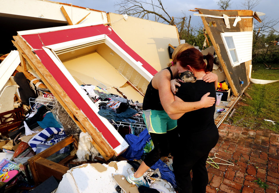 Photo - Alli Christian, left, returns Jessica Wilkinson's dog Bella to her after finding her among the wreckage of Wilkinson's home shortly after a tornado struck near 156th street and Franklin Road on Sunday, May 19, 2013  in Norman, Okla. No one was in the home when the storm struck.  (AP Photo/The Oklahoman, Steve Sisney)