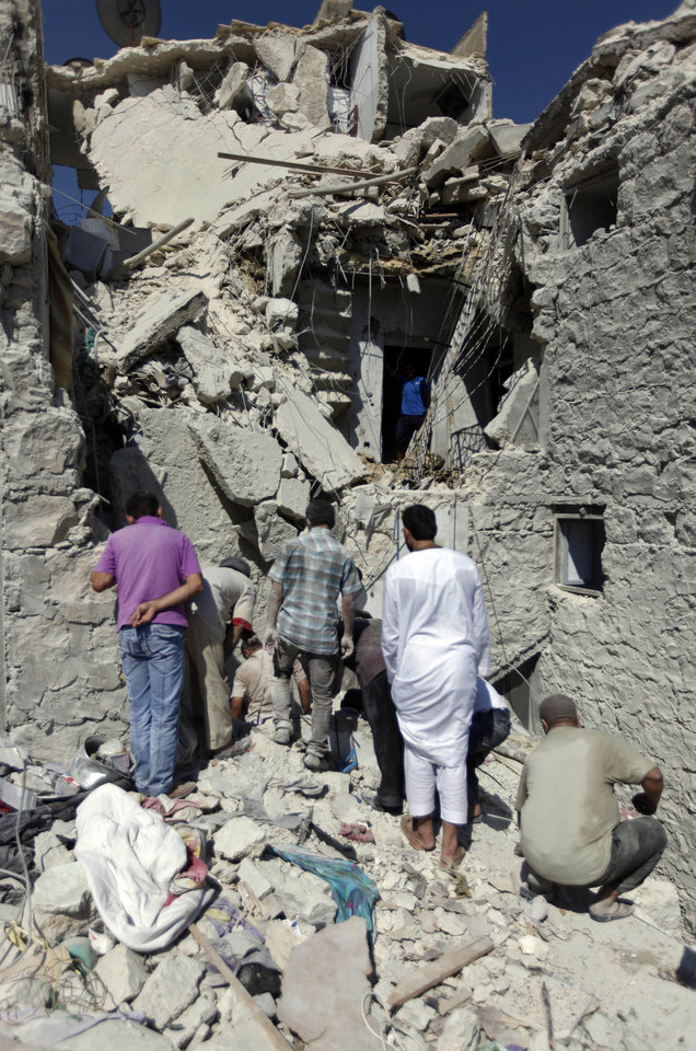 Photo -   Syrians search for the bodies of two girls thought to be under the rubble of a building hit during an airstrike by Syrian government forces in Aleppo, Syria, Sunday, Aug. 19, 2012 (AP Photo/ Khalil Hamra)