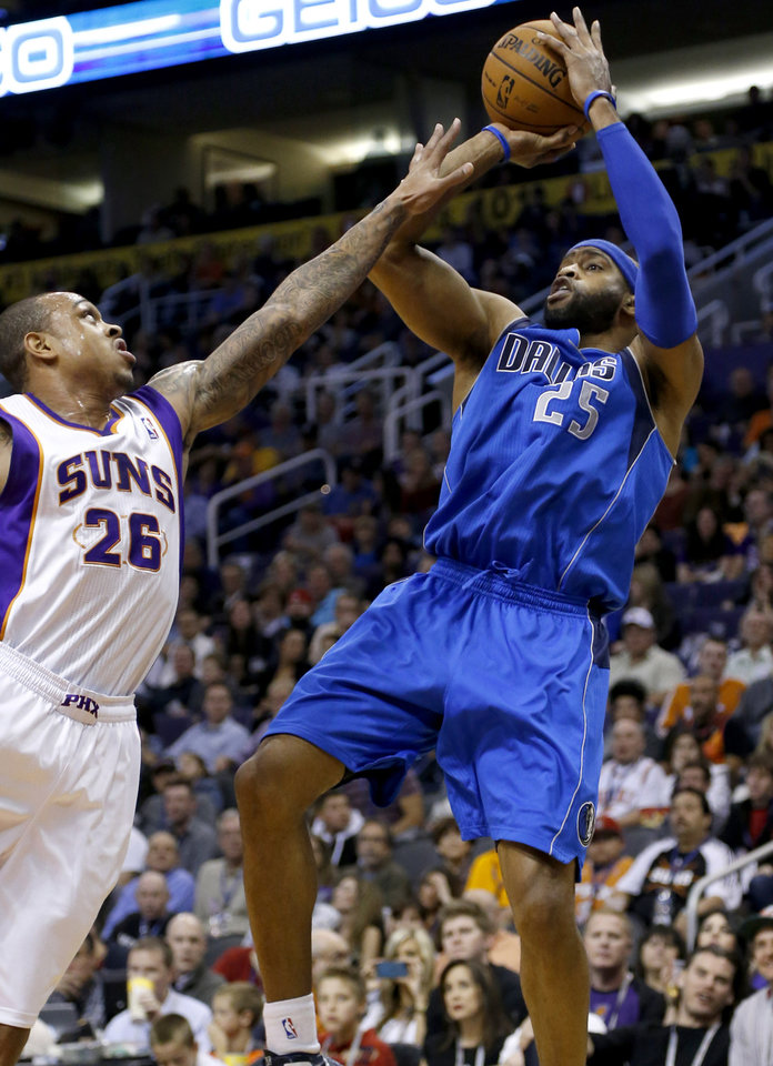 Dallas Mavericks' Vince Carter (25) shoots over Phoenix Suns' Shannon Brown (26) during the first half of an NBA basketball game Friday, Feb. 1, 2013, in Phoenix. (AP Photo/Matt York)